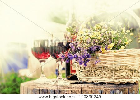 Glasses with red wine and flowers in basket in summer day