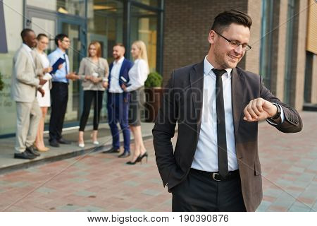 Waist-up portrait of smiling businessman looking at wristwatch while standing at office building and waiting for beginning of conference