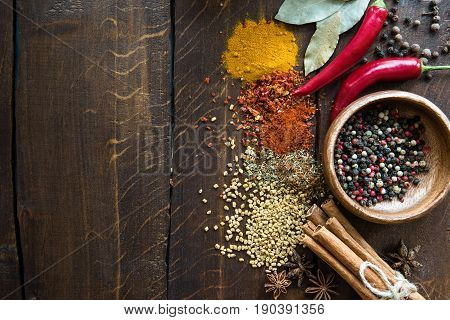 Pepper In Bowl With Scattered Herbs And Spices, Laurel Leaves, Chili Peppers On Wooden Tabletop