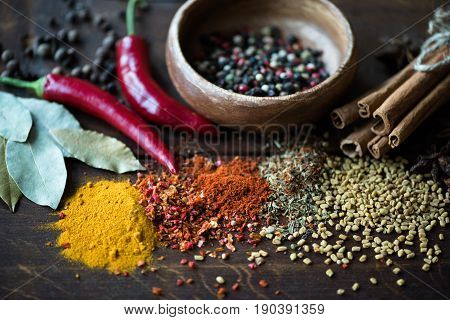 Close Up Of Pepper In Bowl With Scattered Spices, Laurel Leaves, Chili Peppers On Wooden Tabletop