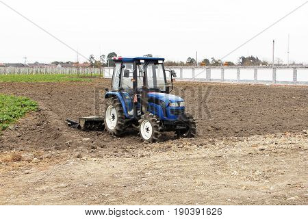 There is a spring ploughing tractor in the field.