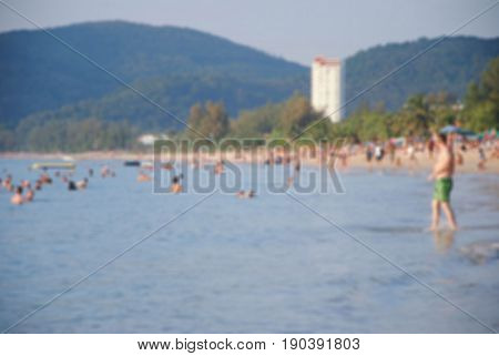 Blurred people on white sand beach with blue sea moutain an sky background