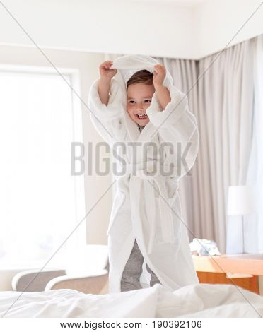 people, childhood and morning concept - happy little boy in bathrobe in bed at home or hotel room