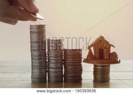 hand take home on pile of money coin in loan concept photo and house finance on wood table