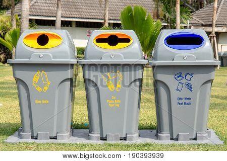 Three plastic Recycle bin in the public park.