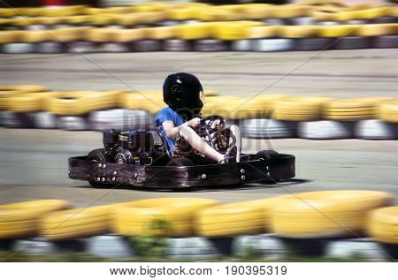 Karting - driver in helmet on kart circuit. motion blurred background to indicate speed
