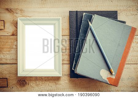Blank white picture frame with old books and pencil put on wooden tabletop background