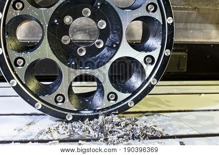 Round car alloy black new rim die mounting in milling and lathe cnc machine. Front view of working process. Mechanical engineering and metalworking industry. Horizontal indoors closeup image.