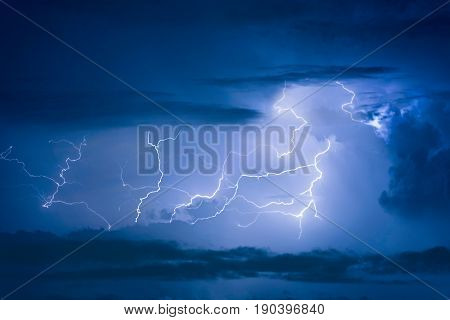 Thunder Storm Lightning Strike On The Dark Cloudy Sky Background At Night.