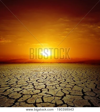 red sunset over drought earth. change of climate
