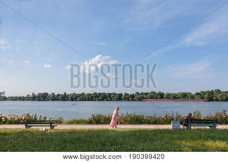 BELGRADE SERBIA - JUNE 03 2017: Old woman walking in front of Danube river in Belgrade on Donji Dorcol district a barge passing by on the water