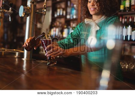 Waitress pouring beer in pilsner glass at counter in pub