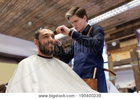 grooming, hairstyle and people concept - man and barber or hairdresser with trimmer cutting hair at barbershop