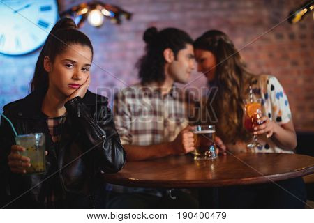 Upset woman ignoring affectionate couple in pub