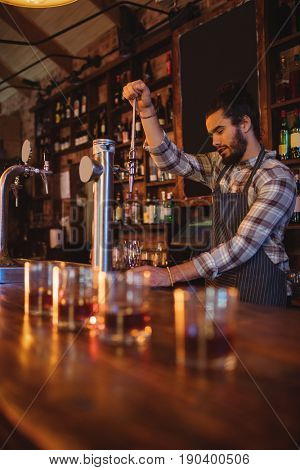 Waiter using beer tap at counter in pub