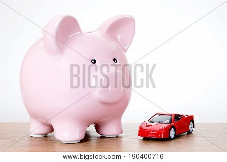Piggy Bank With A Colorful Red Model Toy Car