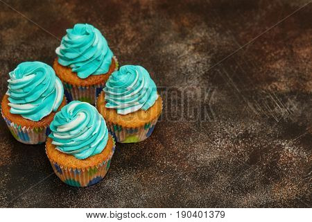 Cupcakes with turquoise and white buttercream frosting dessert on brown background with copyspace
