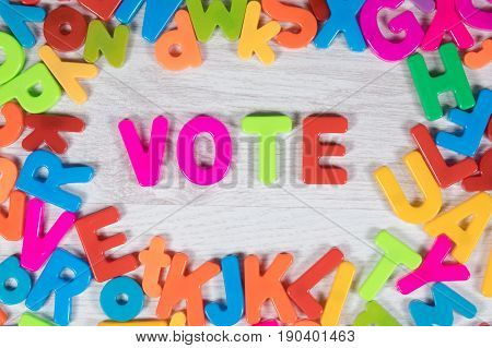 Brightly colored magnet letters create border around the word vote against a white painted wood background