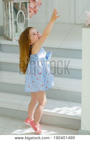 A girl in a blue dress draws her hand to the sky standing on the porch of her house. She hopes that her wish will come true