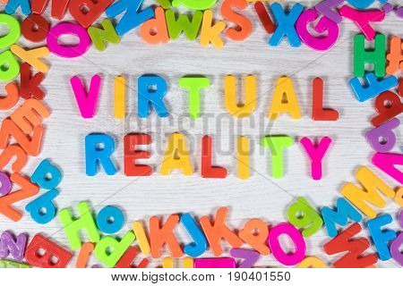 Words virtual reality created with magnet letters and make border against a white painted wood background