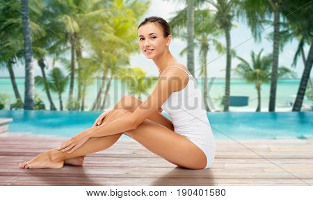 beauty, people and bodycare concept - beautiful woman touching her smooth bare legs over beach and outdoor swimming pool background