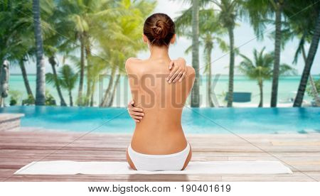 beauty, people and bodycare concept - beautiful topless young woman in white panties sitting on towel from back over beach and outdoor swimming pool background