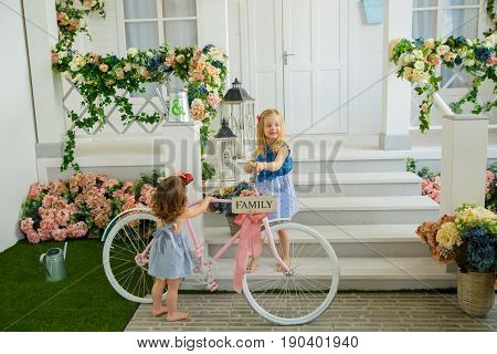Two girls neighbor are talking at the porch about a bicycle arguing who will get a pink bike