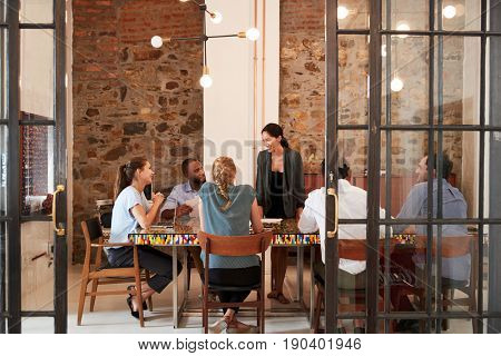 Female boss addressing business team in a meeting room