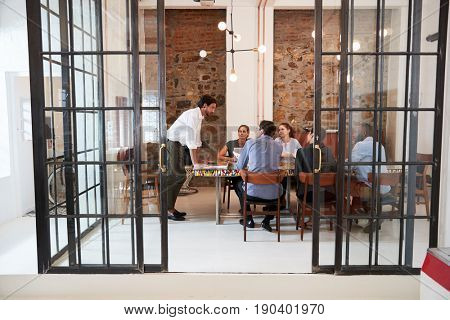 Young man managing a team meeting in a boardroom