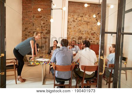 Young woman addressing a team meeting in a boardroom