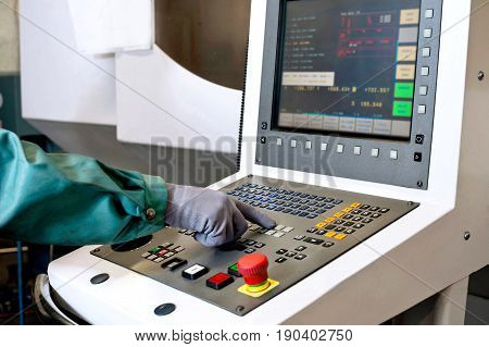 Worker hands on the control panel of a computer numerical control programmable machine. Milling and lathe industry. CNC technology. Metal engineering.