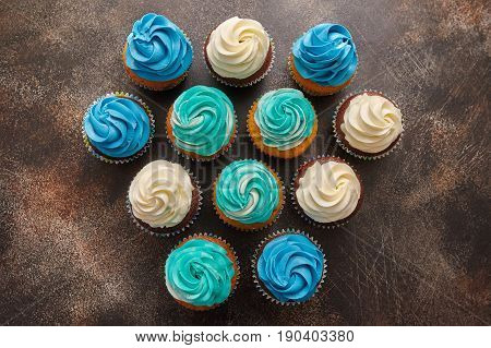 Cupcakes with turquoise and white buttercream frosting dessert on brown background top view