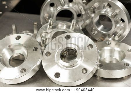 Set of new metal mold of wheel spacers and bolts. CNC milling and lathe industry. Metal engineering. Indoors closeup horizontal image.