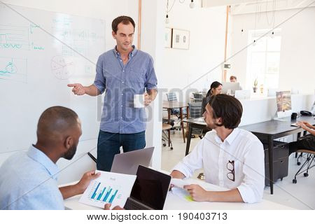 Three men discussing business at whiteboard in a busy office
