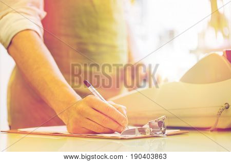 people, sale, retail, business and floristry concept - happy smiling florist man with clipboard and cashbox writing and making notes at flower shop counter