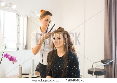 beauty and people concept - happy young woman with hairdresser at hair salon