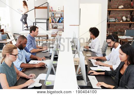Colleagues sit using computers in a busy open plan office