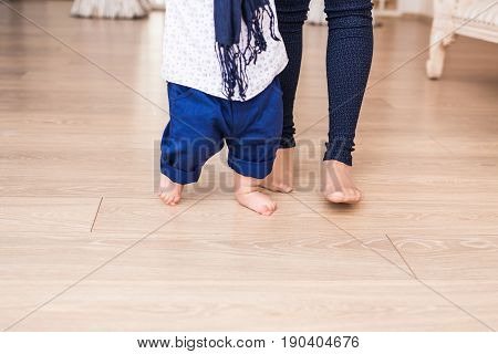 Baby feet doing the first steps. Baby's first steps. Baby feet