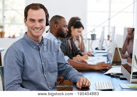 Young white man with headset on smiling to camera in office