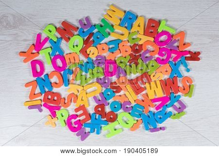 Heap of bright multicolored alphabet letters in the colors of the rainbow for kids in a teaching learning and primary education concept