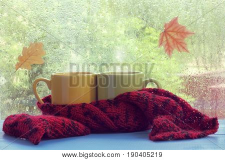 Two mugs wrapped together in a scarf on the background of a window with drops of water / warming pastime in rainy weather