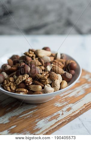 Assorted nuts in white bowl on wooden surface