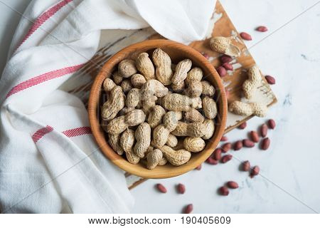Peanuts in wooden bowl on white surface
