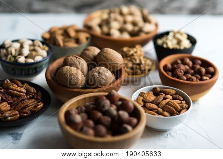 Assorted nuts in wooden bowls on white surface
