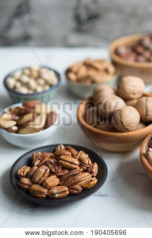 Assorted nuts in different dishes, pecan nuts in focus