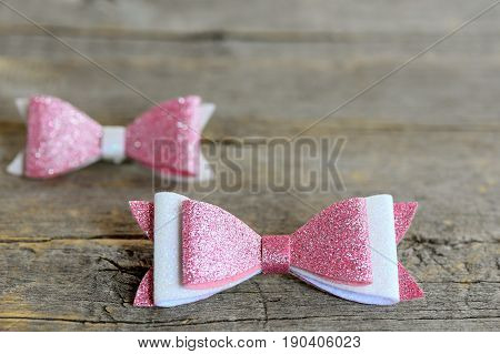 Cute bows for hair. Pink and white shiny felt bows clips for little girls. Nice hair accessories on a wooden background