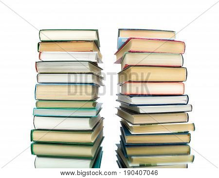 stack of different books on a white background with reflection. horizontal photo.