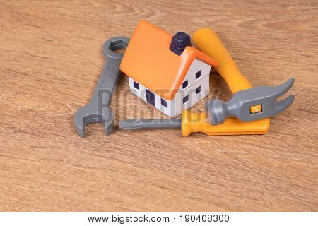 Toy Tools Surrounding Small Plastic House