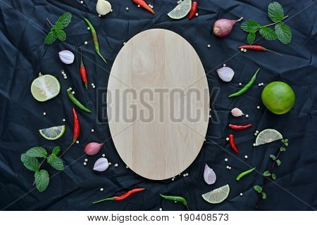 Asian cuisine ingredients food top view spice lemon onion garlic chili pepper mint with Chopping board for cooking original eastern foods style on black fabric texture backgroundThailand food spices