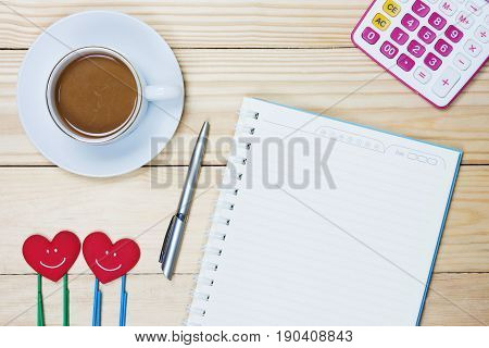 Simple workplace with a cup of coffee notebook paper pen Paper clip and calculator on wood table